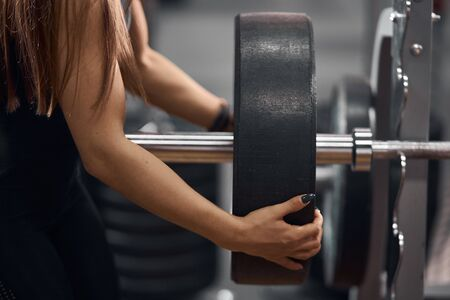 Close view of gentle female hands preparing heavy barbell for training in modern fitness studio, side indoor shot