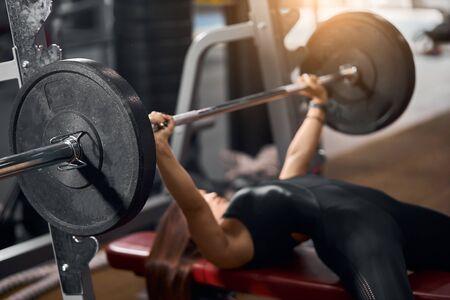 Nahaufnahme einer schwarzen Eisenhantel mit schweren Scheiben in den Händen einer starken Gewichtheberin, die auf einer roten Bank liegt und versucht, im modernen Fitnessclub Bankdrücken zu machen, seitlicher Schuss