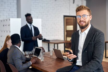 Cheerful young man in tuxedo and eyeglasses using smartphone in workplace while his business colleagues having conversation in background