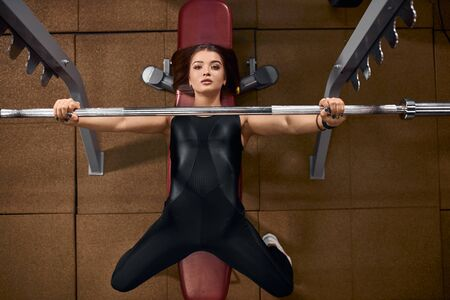 High angle view of charming sportive girl spending evening in modern fitness center, doing exercise for perfect shoulders and arms, workout with iron heavy barbell, looking up with impressive eyes