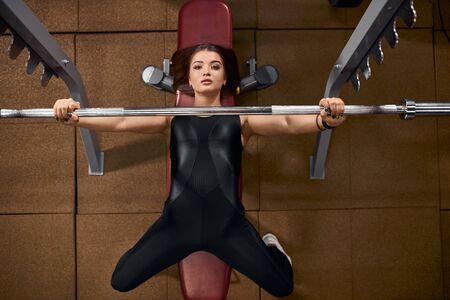 Vista de ángulo alto de encantadora chica deportiva pasando la noche en el moderno gimnasio, haciendo ejercicio para hombros y brazos perfectos, entrenamiento con barra pesada de hierro, mirando hacia arriba con ojos impresionantes