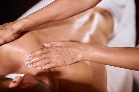Close up of female hands doing aroma massage on male back, professional masseur keeping palms on shoulder of young client, health beauty spa concept Stock fotó