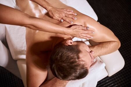Photo of young delighted male client having relaxation body massage from professional male masseur, hands giving body massage, high angle view, reharb massage, indoor shot Stock fotó
