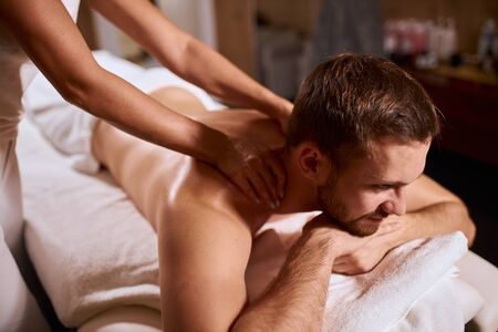 Female hands of professional physiotherapist massaging shoulders and neck of handsome man with thick stylish beard, looking away, having pleasure, expressing satisfaction Stock fotó