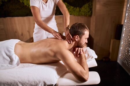High angle shot of young handsome man receiving hand body massage in cosmetology spa center, having pleasure and relaxation, spa health and healing concept Stock fotó