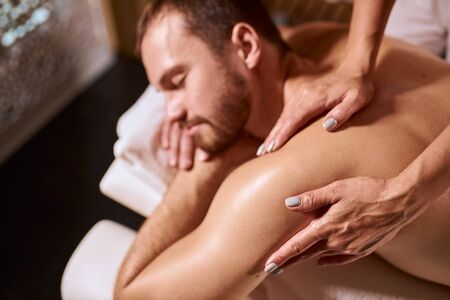 Handsome attractive man with thick stylish beard lying on white soft towels, having aroma therapy massage on black floor, female hands massaging back tenderly, indoor shot Stock fotó