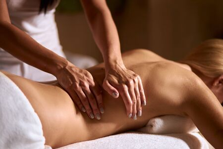 Young blonde woman in wellness beauty spa having aroma therapy massage with essential oil, gentle female hands massaging back of client, total relaxation, close up