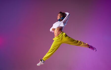 Charming young lady jumping high making acrobatics movies in the air, performing dancing skills, isolated on bright coloured background, urban lifestyle concept