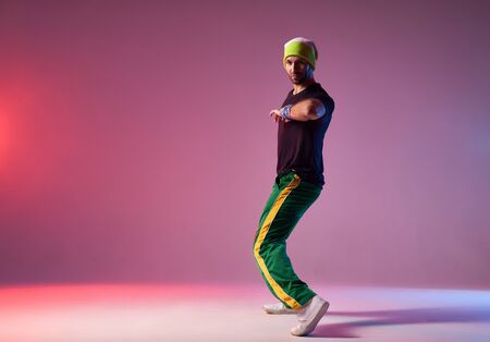 Modern breakdancer in sportive clothes, stretching elbow towards camera, looking away with brutal face, demonstrating dancing skill, posing on pink background
