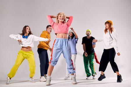 Młody zespół profesjonalnych tancerzy o hun w studio tańca nowoczesnego, aktywnie poruszający się, na białym tle na białym tle, widok z dołu, strzał w pomieszczeniu, koncepcja imprezy tanecznej