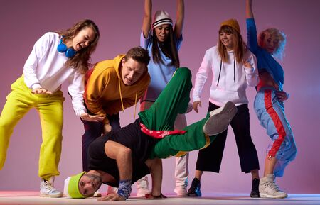 Professional hip hop dancer in motion, leaning on hands, standing upside down, showing break dance for people surrounding dancer, performance in brightly lighted studi