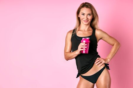 Sporty female model with bottle of water, keeping hand on tight hips, looking at camera with cheerful expression, happy to finish training in fitness studio, drinking water, isolated