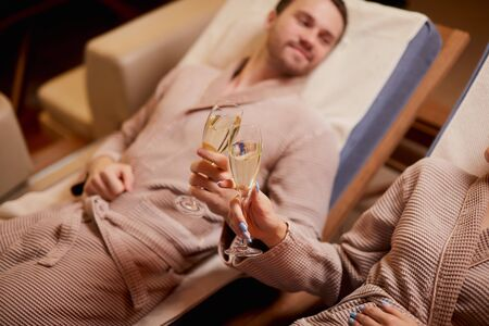 Spending time together in spa salon, fell in love. Married caucasian holding drinking champagne in romantic room in spa center