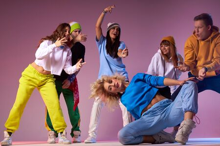 Pretty young blonde girl with long wavy hair, dressed in blue t shirt and sportive pants, sitting on knee on studio floor, training together with active dancers, preparing for concert 版權商用圖片