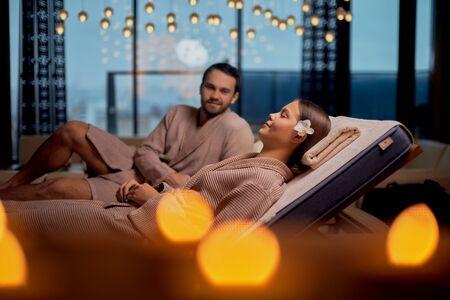 La giovane coppia caucasica si riposa nel salone della spa sdraiato insieme in accappatoio e si rilassa con le candele