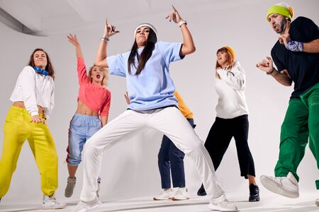 Cool teenagers spending great time on hip hop party, standing in full length, dancing with pleasure, isolated on white colour background, having fun with friends, low angle shot