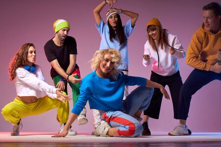 Group of men and women dancing hip hop choreography, showing cheerful expression, enjoying dancing process, screaming with pleasure, training school concept 版權商用圖片