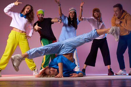 Sportive professional hip hop dancer, standing upside down, doing split legs in the air, playful cheerful people dancing around performing breakdancer