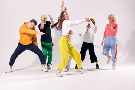Group young funny and happy men and women dancing hip-hop at studio on white color background. Human emotions, youth, love and lifestyle concept