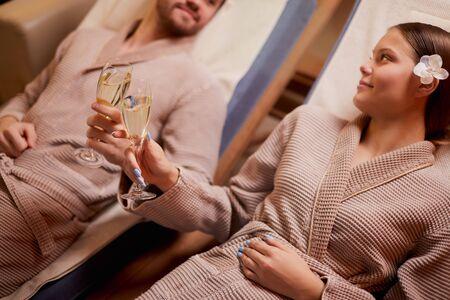 La giovane coppia caucasica si rilassa sui lettini nel centro termale, riposandosi insieme, sdraiati intorno alle candele