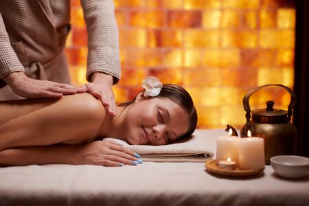 Beautiful caucasian lady came to spa salon to get treatment procedures, massage on her back. Lying down with naked back