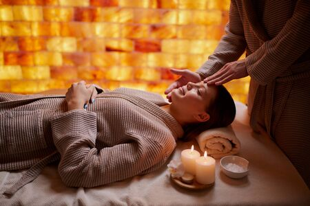 Attractive lady wearing bathrobe lying down on desk for massages, get facial massage in spa salon. Health and body treatment, beauty concept
