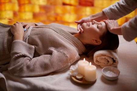Young caucasian lady get reacreation massage of head, face. Lying down on desk for massages wearing bathrobe