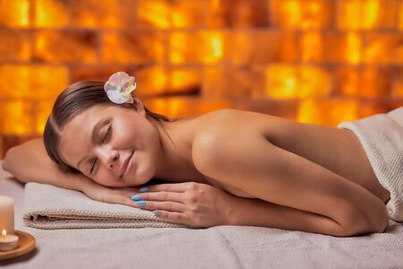 Attractive young lady lying down on her belly in spa salon, getting massage on her back, relaxes woman with flower on head, candles near her.
