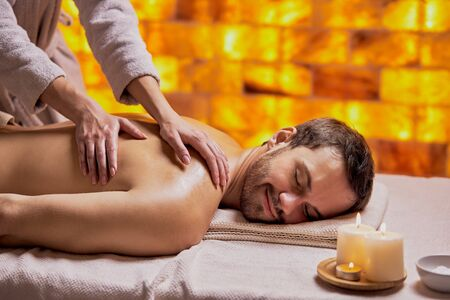 Young caucasian man relax during massage on back made by female hands, lying on spa table, enjoy spa treatment Banque d'images
