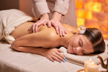 Attractive young female get massage on back lying on table in spa salon, naked back. female hands doing massage, using candles