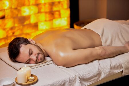 Young Ccaucasian male came to spa salon to relax and get massage on back and shoulders , lying on spa table