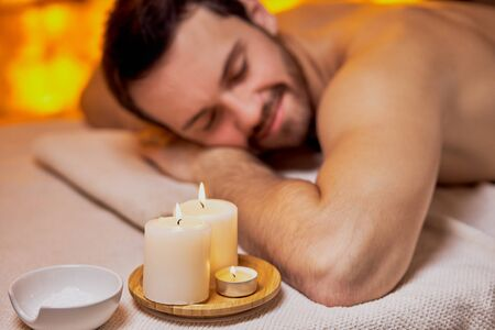 Handsome caucasian lying after massage in the beauty salon, spa salon, naked skin. Young bearded man relaxing,yellow wall background in spa