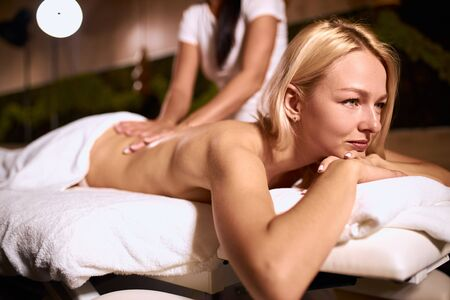 Pretty charming lady getting back massage from thai girl in spa salon, looking away with calm relaxed face, total relaxation, shot from below, close up