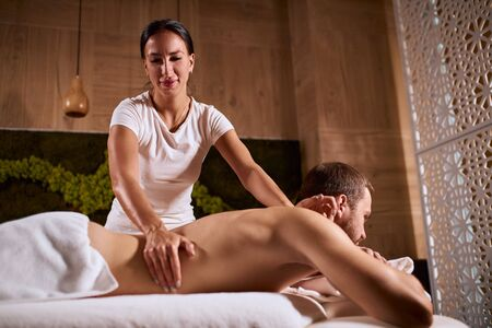 Professional physiotherapist working in medical clinic with client, massaging male back, giving hand massage, looking down with pleasant face, enjoying process of work