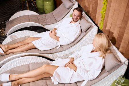 High angle view of smiling beautiful man passionately talking to young blonde girl in beauty treatment spa center, dressed in white bathrobe, wearing slippers, looking away with positive emotions
