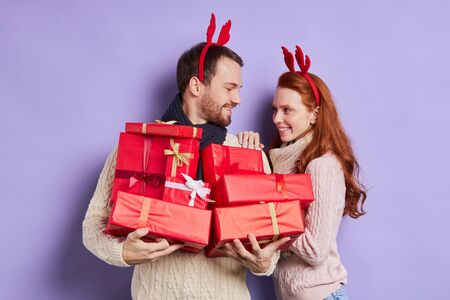 Charming pretty couple preparing for New Years Eve, holding beautiful christmas presents, going to put gifts under green fir, looking away, enjoying time together, family portrait