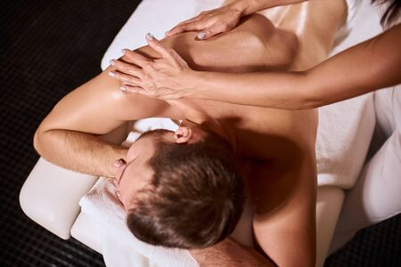 Satisfied male client lying on white fresh soft towels, receiving hand massage from female massage therapist, background of black floor of modern wellness center, high angle view, indoor shot Stock Photo