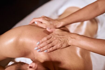 Gentle female hands of professional thai masseur putting palms on male back, giving tissue massage, satisfaction and pleasure concept in cosmetology spa salon, close up, side shot