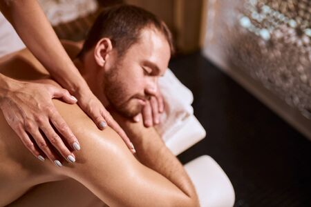 Portrait of impressive young man getting hand massage from professional female physiotherapist in medical clinic, spa health and healing, black floor background Stock Photo
