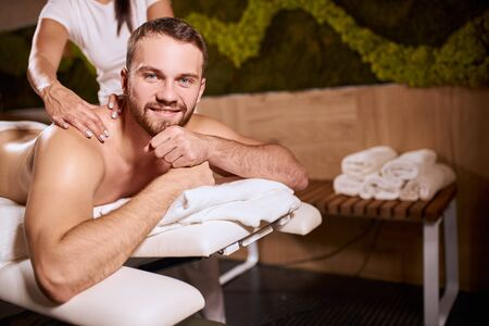 Sports massage. Female massage therapist massaging shoulders of a male athlete, working with Trapezius muscle, in cosmetology spa center, charming man looking at camera, touching chin, indoor shot