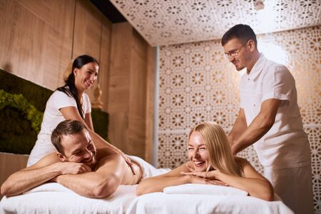 Charming young couple relaxing at beauty spa center, enjoying time together, receiving hand aroma therapy massage, lying on white towels, low angle shot, health treatment concept, talking joyfully