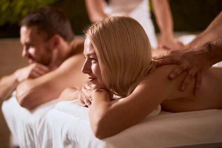 Pleasant attractive woman with long blonde hair lying on massage couch, having pleasure, silently looking away with satisfied eyes, spa health and healing concept