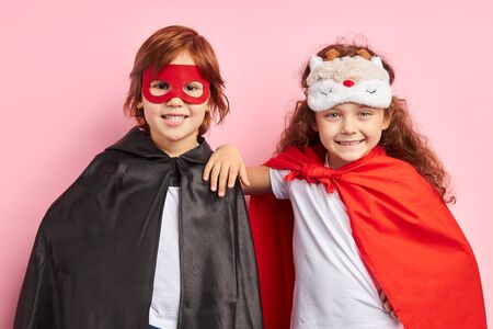 Two cheerful children wearing cloaks and mask, imagine themselves as heroes. Portrait, isolated over pink background