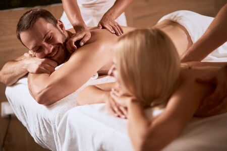 Young lovely couple chatting happily in thai massage center, looking at each others, smiling broadly, blonde woman turning head towards unshaven guy, listening attentively, wellness wellbeing concept