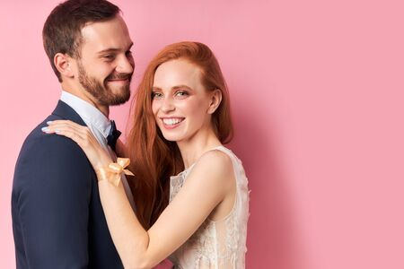 Portrait of redhaired woman in white dress and bearded man in suit hugging each other, isolated pink background