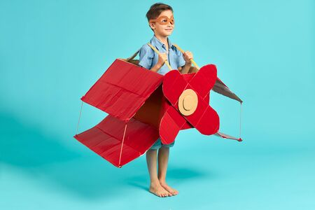Little caucasian boy flying on red carboard airplane, happy boy in casual clothes imagine himself as pilot. Isolated blue background, sky