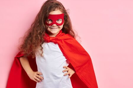 Portrait of confident smiling kid superhero wearing red cloak and mask on eyes imagines herself as hero, stand isolated ove pink background