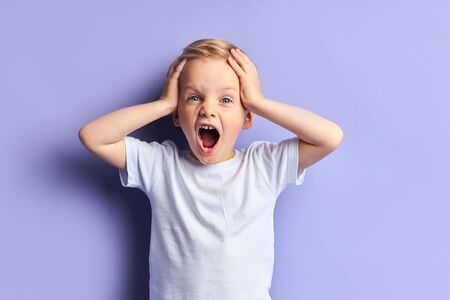 Blond boy screaming, with opened mouth. Wearing white t-shirt, purple background