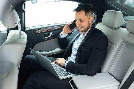 Bel homme barbu travaillant sur ordinateur portable tout en parlant au téléphone dans sa voiture de luxe, vue latérale