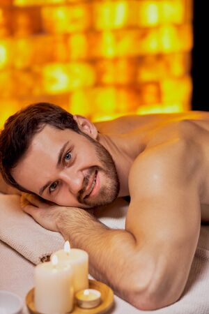 Portrait of young caucasian man lying on massage table at spa center with naked skin, massage on back and shoulders. Smile and look at camera, take pleasure from spa procedures Фото со стока